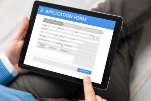 Sample application form on tablet computer, man using tablet